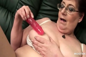 aged playgirl in glasses using her sex toys to